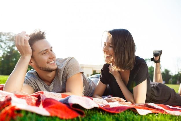 Het jonge mooie paar glimlachen, die op picknick in park rusten.