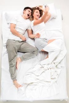 Het jonge mooie paar liggend in een bed met telefoon, liefde lconcept, bovenaanzicht