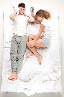 Het jonge mooie paar liggend in een bed met wekker