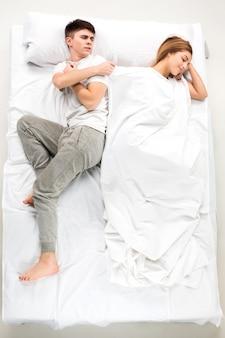 Het jonge mooie paar liggend in een wit bed, liefde lconcept, bovenaanzicht