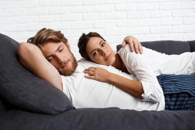 Het jonge mooie paar ontspannende rusten die thuis op bank liggen.