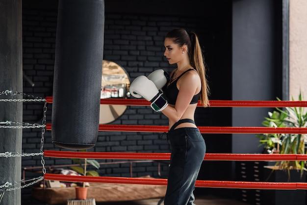 Het jonge mooie sportenmeisje in sportkleding en bokshandschoenen raakt een bokszak in moderne zwarte gymnastiek.