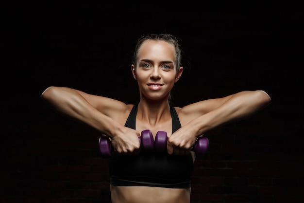 Het jonge mooie sportieve meisje glimlachen, die over donkere muur opleiden