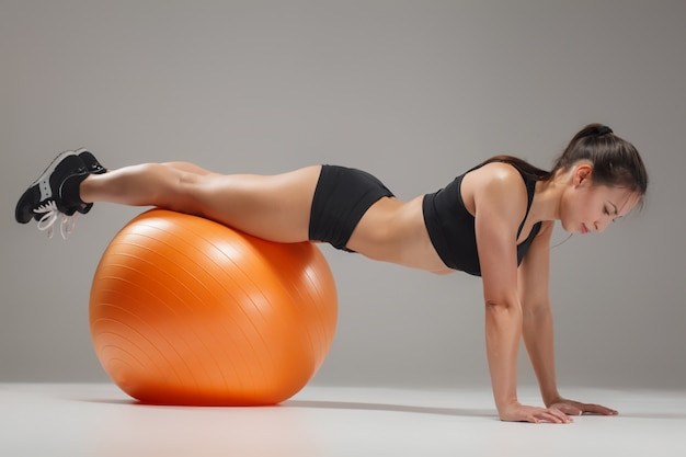Het jonge, mooie, sportmeisje doet oefeningen op een fitball
