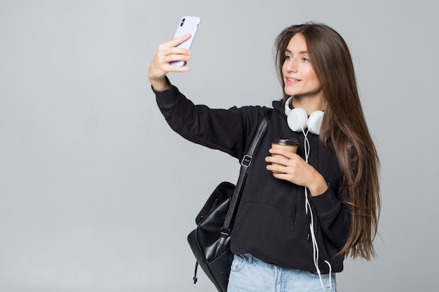 Het jonge mooie studentenmeisje met rugzak maakt selfie geïsoleerd op witte muur in studio