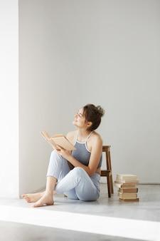 Het jonge mooie tedere vrouw glimlachen die het boekzitting van de vensterholding op vloer over witte muur vroeg in de ochtend bekijken.