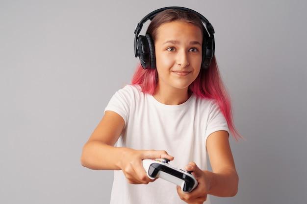 Het jonge mooie tienermeisje spelen met consolebedieningshendel over een grijze achtergrond