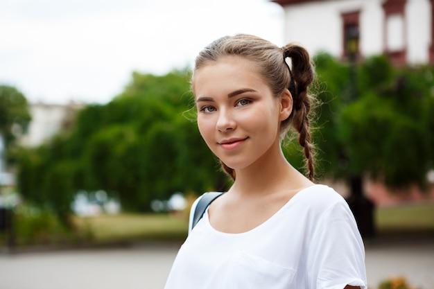 Het jonge mooie vrolijke vrouwelijke student glimlachen, die omslagen in openlucht houdt.