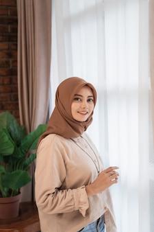 Het jonge mooie vrouw gesluierde glimlachen kijkt de camera die zich dichtbij gordijnenvensters bevindt