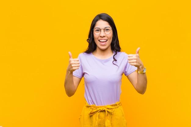 Het jonge mooie vrouw glimlachen die in het algemeen gelukkig, positief, zeker en succesvol kijkt, met beide duimen tegen oranje muur