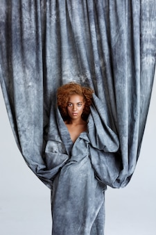 Het jonge mooie vrouw stellen, die zich in grijze doek verpakken