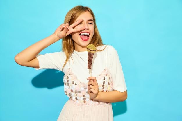 Het jonge mooie vrouw zingen met steunen valse microfoon. trendy vrouw in casual zomerkleding. grappig model dat op blauwe muur wordt geïsoleerd