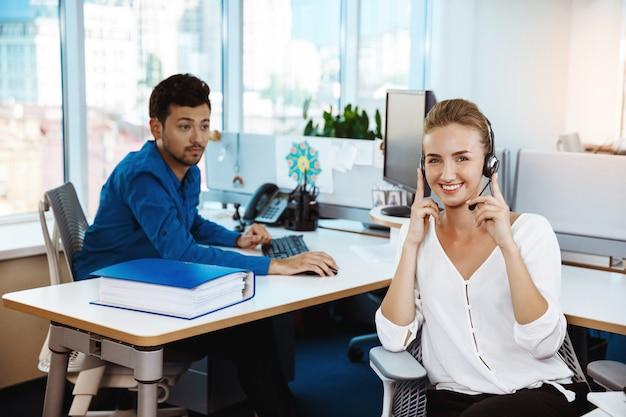 Het jonge mooie vrouwelijke exploitant van de steuntelefoon spreken, die over bureau raadplegen