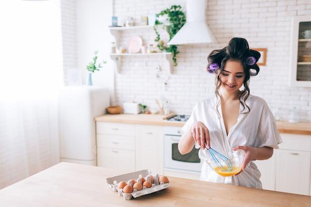 Het jonge mooie vrouwelijke huishoudster koken in keuken. eieren mengen in glazen kom. kijk naar beneden en glimlach. krulspelden in haar. alleen in de keuken. daglicht. draag witte kamerjas.