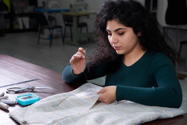 Het jonge naaiende jasje van de vrouwennaaister bij studio terwijl het zitten op haar werkende plaats. modeontwerper in kleermakerij