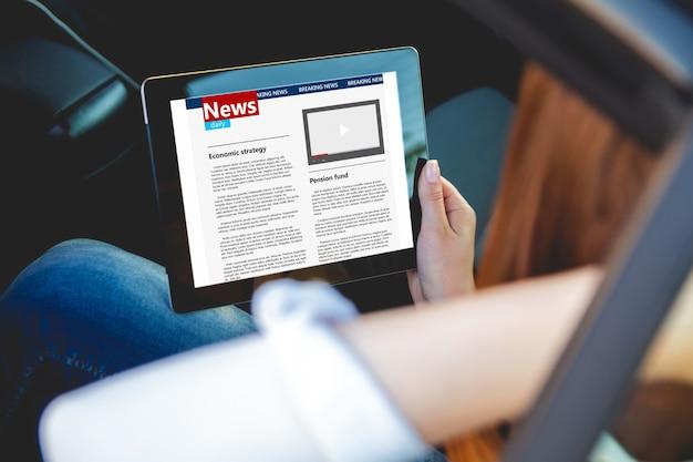 Het jonge nieuws van de vrouwenlezing met tablet in handen die in auto zitten