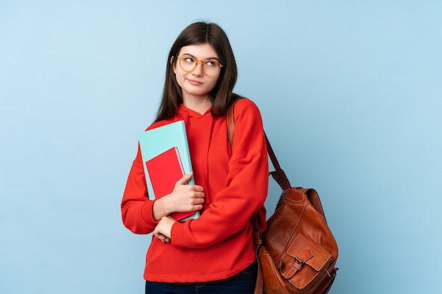 Het jonge oekraïense meisje die van de tienerstudent een salade over geïsoleerde blauwe muur houden die een idee denken