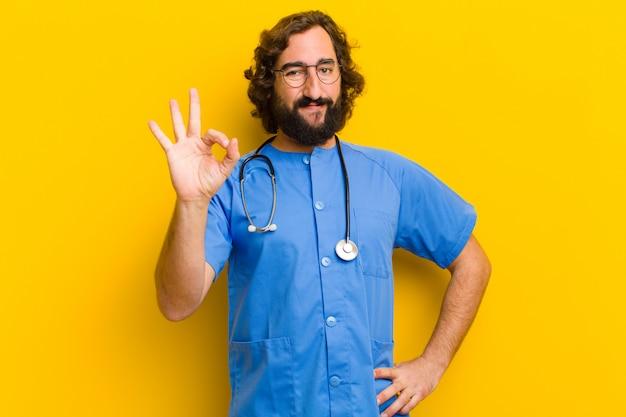 Het jonge ok gebaar van de verpleegstersmens tegen gele muur