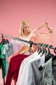 Het jonge ongelukkige mooie meisje dat jurken bekijkt en het probeert terwijl het kiezen bij winkel