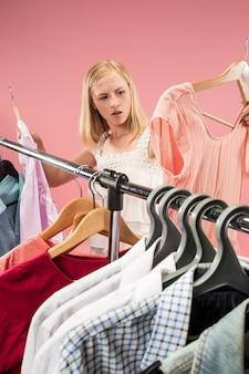 Het jonge, ongelukkige mooie meisje kijkt naar jurken en probeert het terwijl ze in de winkel kiest