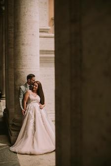 Het jonge onlangs gehuwde paar stellen in rome met mooie en oude architectuur op de achtergrond