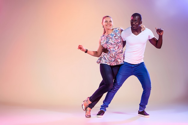 Het jonge paar danst sociale caraïbische salsa, studioschot