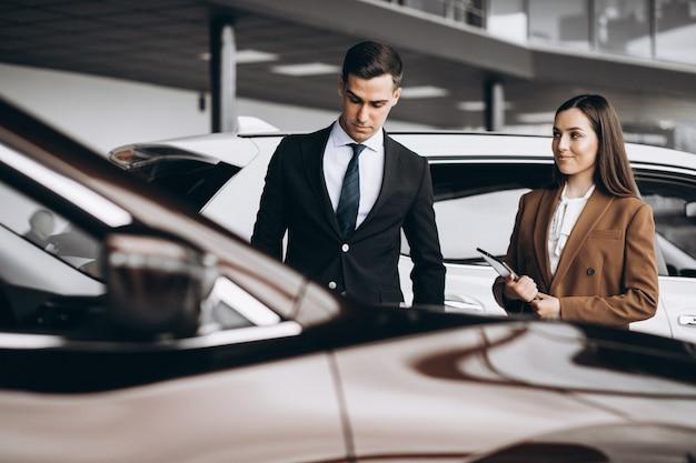 Het jonge paar dat een auto in een auto kiest toont ruimte