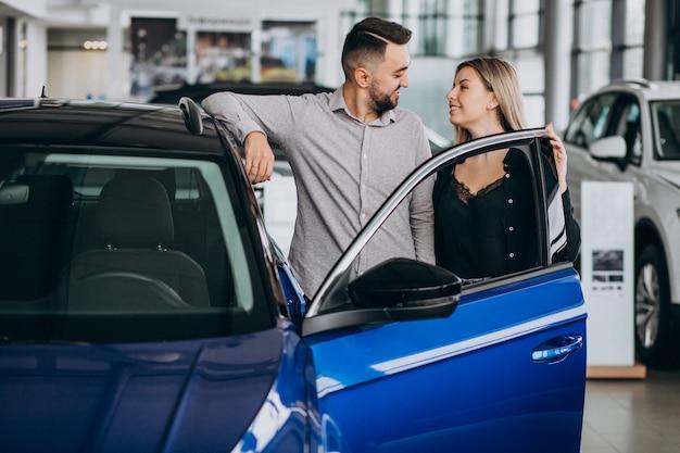 Het jonge paar dat een auto in een autoshowruimte kiest