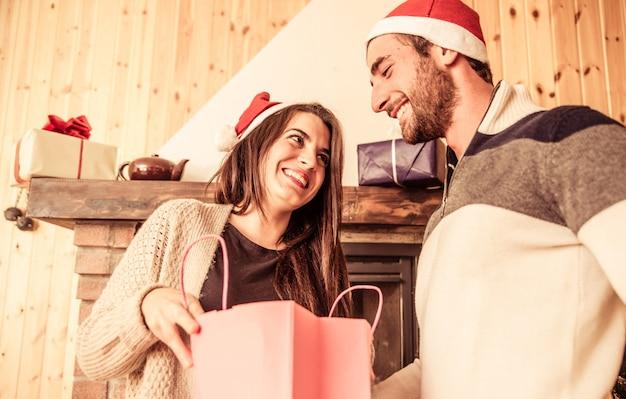 Het jonge paar dat kerstmis deelt stelt voor