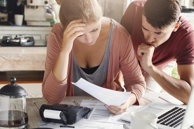 Het jonge paar die hun binnenlands budget samen in keuken berekenen, proberen geld te besparen voor het kopen van nieuwe auto, hebben beklemtoonde en gefrustreerde blikken. ongelukkige vrouw die onbetaalde rekening toont aan haar echtgenoot