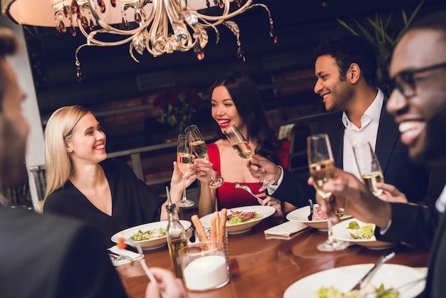 Het jonge paar drinkt in restaurant met vrienden