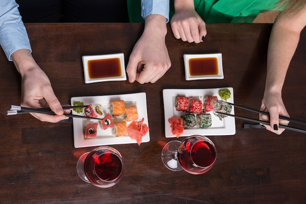 Het jonge paar eet sushi bij restaurant.