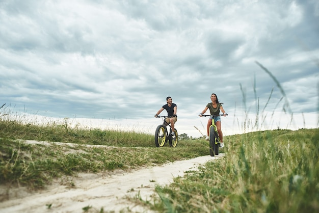 Het jonge paar fietst op het vooraanzicht van de groene heuvels