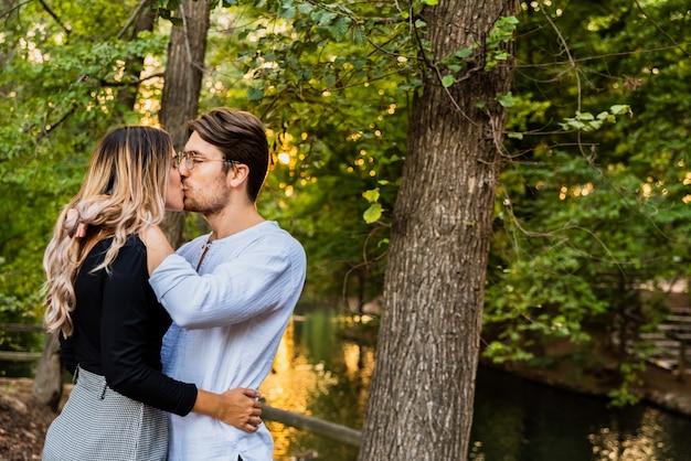Het jonge paar geeft hun eerste kus in een park bij zonsondergang, concept het vallen in liefde.