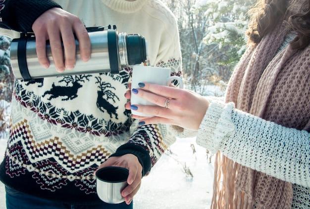 Het jonge paar giet hete thee uit thermosflessen in bos