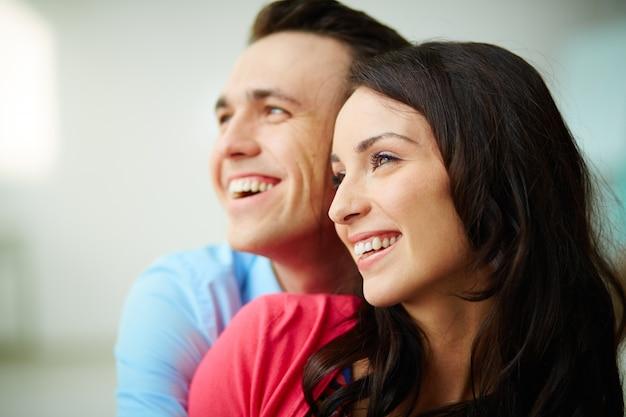 Het jonge paar glimlachen bij elkaar