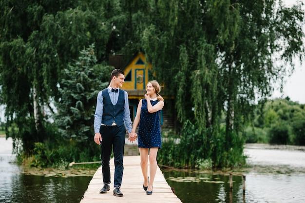 Het jonge paar hand in hand, gaan op een houten brug boven het meer op de achtergrond