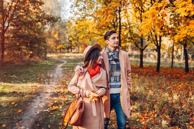 Het jonge paar in liefde loopt in de herfstbos onder kleurrijke bomen. man en vrouw knuffelen buitenshuis bij zonsondergang