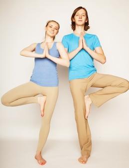 Het jonge paar in yoga stelt, gelukkige familie