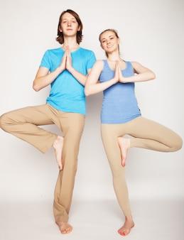 Het jonge paar in yoga stelt