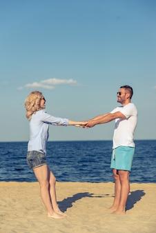 Het jonge paar in zonglazen houdt handen.