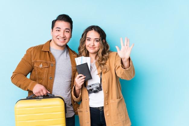 Het jonge paar klaar voor een reis isoleerde glimlachend vrolijk tonend nummer vijf met vingers.