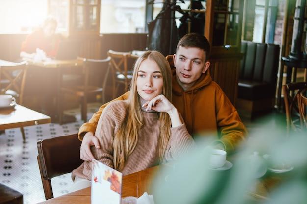 Het jonge paar kleedde samen warme vrijetijdskledingszitting bij koffie