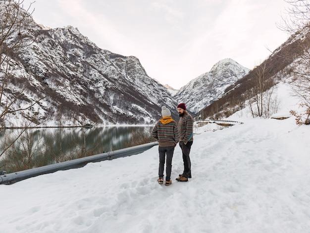 Het jonge paar kleedde zich gelijk in de winterkleren op besneeuwde berg naast een bevroren meer.