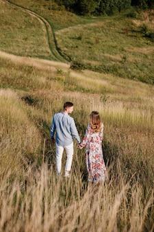 Het jonge paar koestert binnen liefde openlucht. prachtig sensueel buiten portret van jonge stijlvolle mode paar poseren in de zomer in veld.