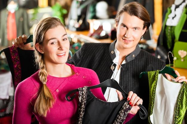 Het jonge paar koopt tracht of dirndl in een winkel