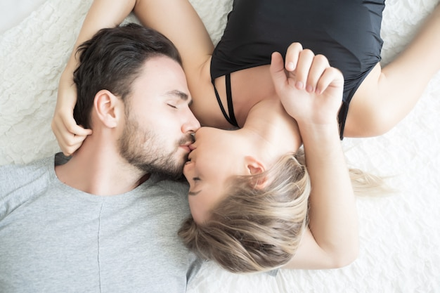 Het jonge paar kussen in het bed. liefdevol paar in de slaapkamer