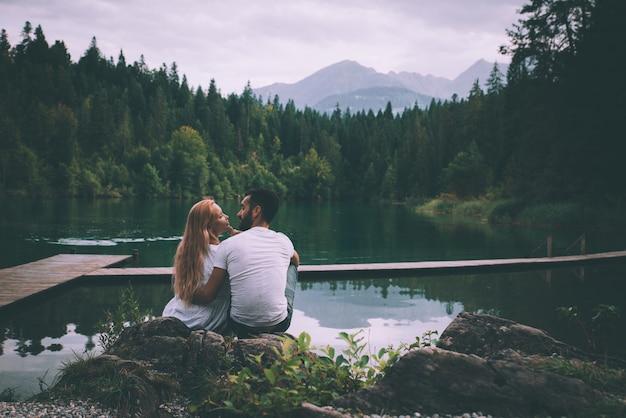 Het jonge paar kussen vooraan mooi meerlandschap