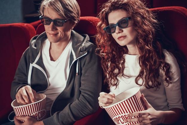 Het jonge paar met 3d glazen eet popcorn.