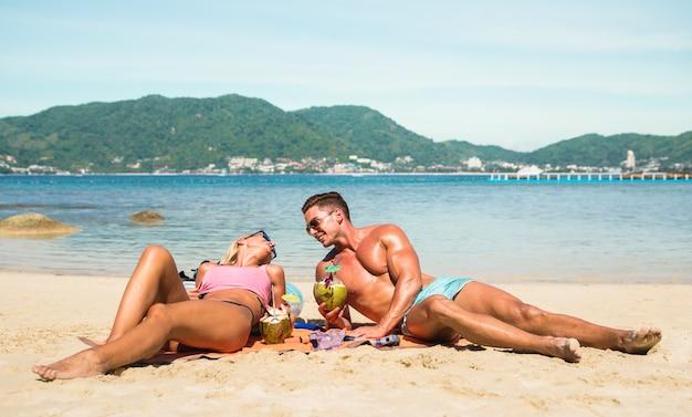 Het jonge paar ontspannen bij tropisch strand in thailand
